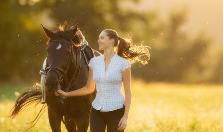 Young woman running with her horse in evening sunset light. Outdoor photography with fashion model girl. Stock Photo