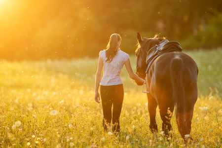 夕方には夕日の光の彼女の馬と一緒に歩いている若い女性の Backview。ファッションのモデルの少女と野外撮影。