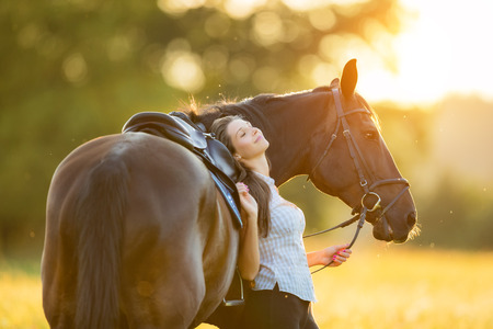 Young woman relaxing with her horse in evening sunset light. Outdoor photography with fashion model girl. Stock Photo