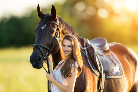 Young woman with her horse in evening sunset light. Outdoor photography with fashion model girl. photo