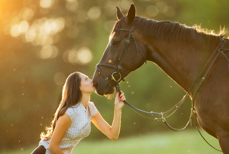 Young woman with her horse in evening sunset light. Outdoor photography with fashion model girl.