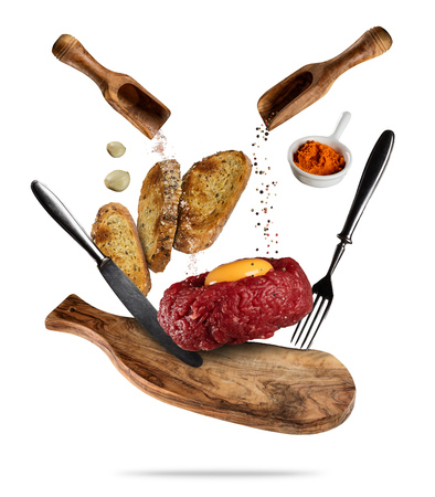 Flying tartar steak with spice and toasts. Concept of flying food in low gravity. Very high resolution image. Isolated on white background Stock Photo - 82699986