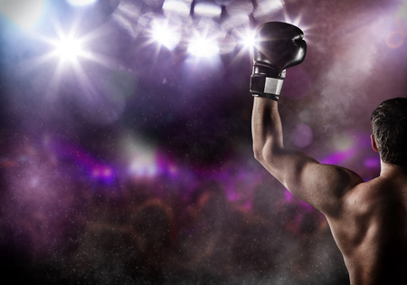 Close-up of man boxer with raised hand in victory gesture. Concept of hard sport, glory and success. Free space for text. High resolution image Stock Photo