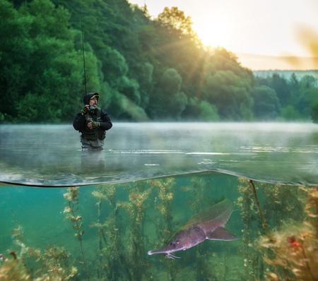 Visser probeert roofdiervissen te vangen, half tot halve beeldspraak. utdoor vissen in de rivier tijdens zonsopgang. Jacht- en hobbysport. Onderwater leven Stockfoto