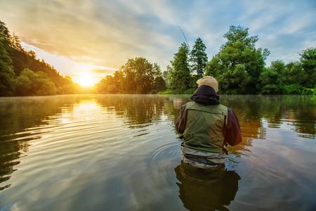 スポーツの漁師の狩猟捕食者の魚。屋外日の出中に川で釣り。狩猟や趣味のスポーツ。 写真素材