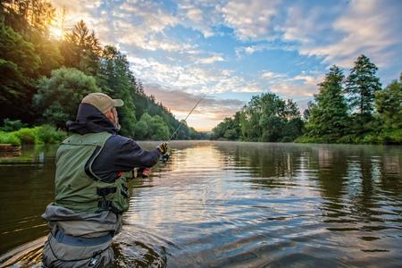 Pêcheur sportif chassant le poisson prédateur. Pêche en plein air dans la rivière pendant le lever du soleil. Chasse et sport amateur. Banque d'images