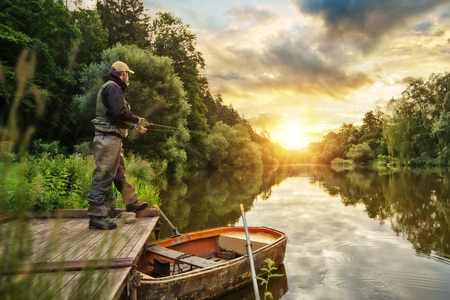 나무 부두에서 스포츠 어부 사냥 포식 동물 물고기. 일출 동안 강에서 야외 낚시입니다. 사냥과 취미 스포츠.