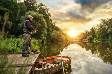 Pescatore sportivo caccia predatore di pesce dal molo di legno. Pesca all'aperto nel fiume durante l'alba. Caccia e sport per hobby. Archivio Fotografico - 83602457