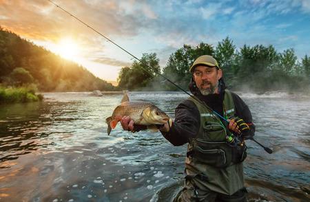スポーツ トロフィーの魚を手にする漁師。屋外日の出中に川で釣り。狩猟や趣味のスポーツ。 写真素材