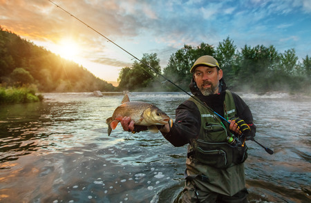 Sport fisherman holding trophy fish. Outdoor fishing in river during sunrise. Hunting and hobby sport.