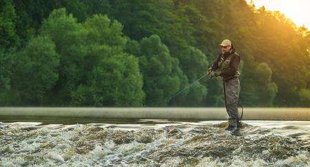 스포츠 어부 사냥 물고기입니다. 일출 동안 강에서 야외 낚시입니다. 사냥과 취미 스포츠. 스톡 콘텐츠 - 83602464