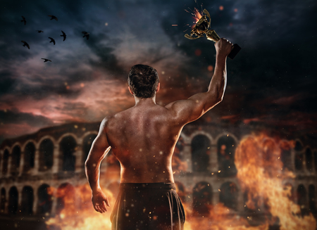 Back view of muscular man holding burning trophy cup, antique colosseum on background. Concept of success, hard work and conquest of the target. Very high resolution image Zdjęcie Seryjne