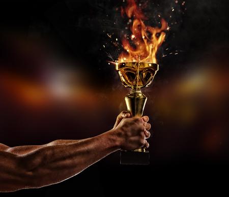Bras de l'homme musclé tenant coupe trophée brûlante sur fond noir. Détail de la main de combattant. Concept de réussite, travail acharné et conquête de la cible. Haute résolution