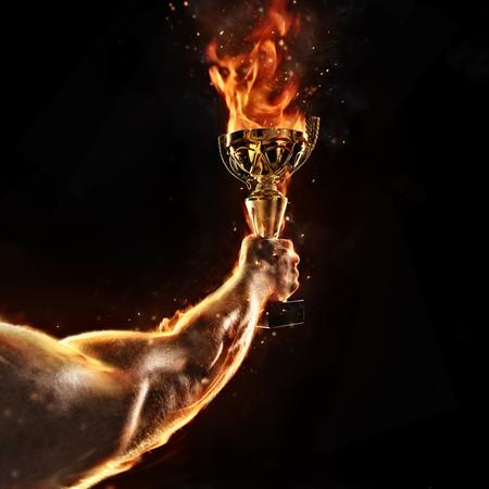 Gespierde man arm houden brandende trofee cup op zwarte achtergrond. Detail van jagerhand. Concept van succes, hard werken en verovering van het doelwit. Hoge resolutie