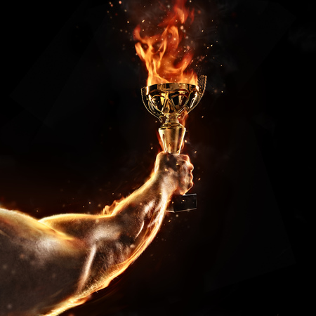 Muscular man arm holding burning trophy cup on black background. Detail of fighter hand. Concept of success, hard work and conquest of the target. High resolution Stock fotó - 83596016