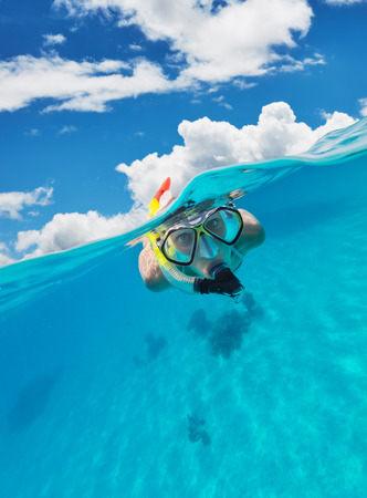 Snorkeling woman exploring ocean sealife, under and above water photography. Travel lifestyle, water sport outdoor activities, swimming and snorkeling on summer beach holidays.