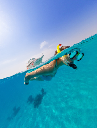 Snorkeling woman exploring ocean sealife, under and above water photography. Travel lifestyle, water sport outdoor activities, swimming and snorkeling on summer beach holidays. Banco de Imagens - 84346522