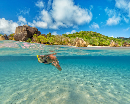 Snorkeling woman exploring beautiful ocean sealife, under and above water photography. Travel lifestyle, water sport outdoor activities, swimming and snorkeling on summer beach holidays. Stock Photo
