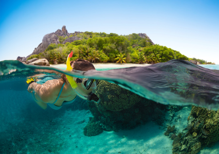 Snorkeling woman exploring beautiful ocean sealife, under and above water photography. Travel lifestyle, water sport outdoor activities, swimming and snorkeling on summer beach holidays. Banco de Imagens - 84346531