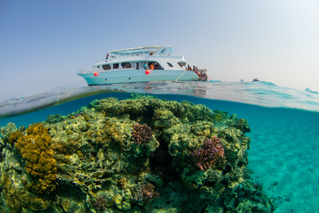 ocean waves: Small safari boat with snorkelists ready to jump into the water. Beautiful split shot under and above water. Travel lifestyle, water sport outdoor activities, swimming and snorkeling Stock Photo