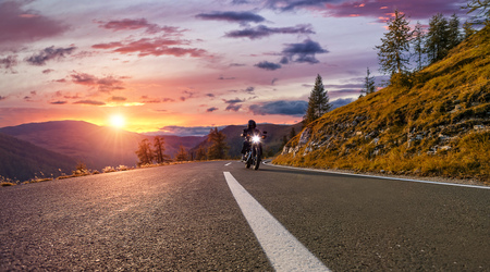 Motorcycle driver riding in Alpine highway,  Nockalmstrasse, Austria, Europe. Outdoor photography, mountain landscape. Travel and sport photography. Speed and freedom concept Banque d'images