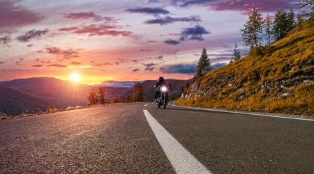 Guidatore di motociclismo in autostrada alpina, Nockalmstrasse, Austria, Europa. Fotografia all'aperto, paesaggio montano. Fotografia di viaggio e sport. Concetto di velocità e libertà Archivio Fotografico - 84981824