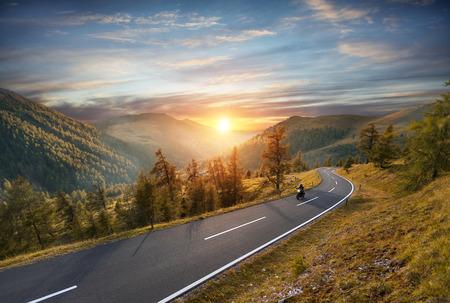 Motociclista che guida in autostrada alpina, Nockalmstrasse, Austria, Europa. Fotografia all'aperto, paesaggio montano. Viaggi e fotografia sportiva. Concetto di velocità e libertà Archivio Fotografico - 84981825