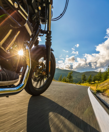 Detail of motorcycle front wheel. View from co-driver perspective, beautiful Alpine landscape in sunset light. Travel and sport photography in outdoor. Speed and freedom concept