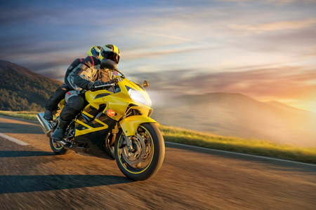 Motorbikers on sports motorbike riding in alpine landscape. Outdoor photography, European mountains. Travel and sport photography. Speed and freedom concept