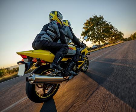 Motorrijders op sportmotorfiets het berijden in zonsondergang. Buitenfotografie, Europees landschap. Reis- en sportfotografie. Snelheid en vrijheid concept