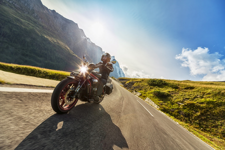 Motorcycle driver riding in Alpine highway,  Hochalpenstrasse, Austria, Europe. Outdoor photography, mountain landscape. Travel and sport photography. Speed and freedom concept