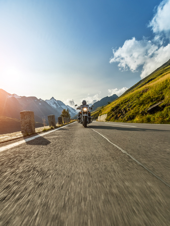 Motorcycle driver riding in Alpine highway,  Hochalpenstrasse, Austria, Europe. Outdoor photography, mountain landscape. Travel and sport photography. Speed and freedom concept Stock Photo - 85491781