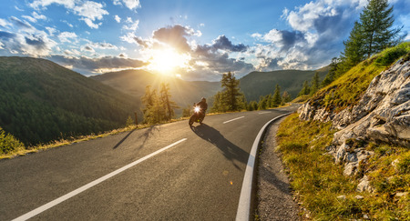 Motorcycle driver riding in Alpine highway,  Nockalmstrasse, Austria, Europe. Outdoor photography, mountain landscape. Travel and sport photography. Speed and freedom concept Foto de archivo