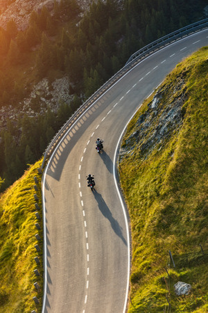 curve road: Motorcycle drivers riding in Alpine highway,  Hochalpenstrasse, Austria, Europe. Outdoor photography, mountain landscape. Travel and sport photography. Speed and freedom concept