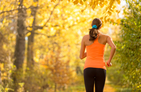 Young brunette woman running in autumn forest. Lifestyle and sport photo of healthy style. Outdoor and nature fitness exercise. Stock Photo