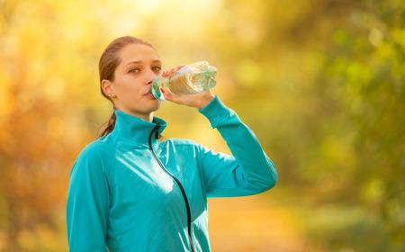 秋に彼女のフィットネス運動中にボトルから新鮮な水を飲む若い女性。健康的なスタイルのライフ スタイルとスポーツの写真。自然と屋外フィット