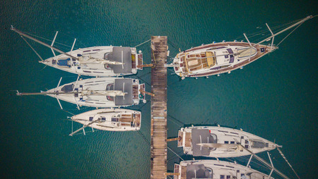 Group of sailing boats anchoring in marina next to jetty wooden pier. Aerial photo, high angle of view, bird eye perspective