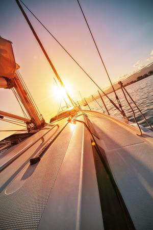 美しい夕日に対するヨットセーリングのクローズアップ。スポーツとレクリエーションの追求。海での野外活動。