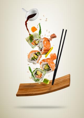 Vliegende sushi stukken geserveerd op houten plaat, gescheiden op zachte achtergrond. Veel soorten populair sushi eten met eetstokjes. Zeer hoge resolutie afbeelding