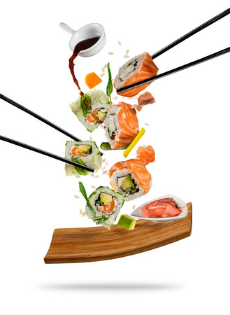 Sushi pieces placed between chopsticks, separated on white background. Popular sushi food. Very high resolution image Foto de archivo