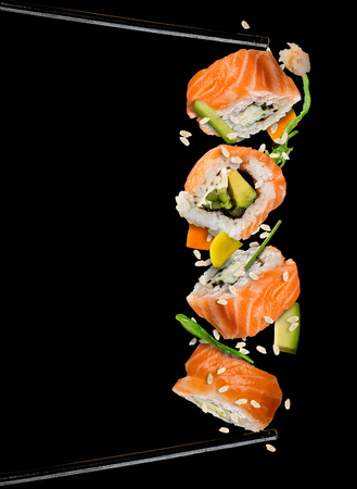 초밥 조각 검정색 배경에 구분 된 젓가락 사이 배치합니다. 인기있는 스시 음식. 매우 높은 해상도 이미지