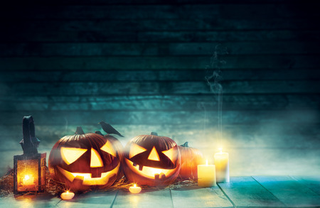 Spooky halloween pumpkins on wooden planks in dark cellar. Celebration theme, copyspace for text. Very high resolution image