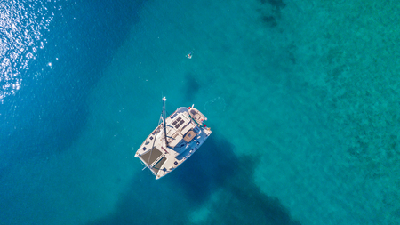 Aerial view of catamaran anchoring on coral reef. Bird eye view, water sport theme.