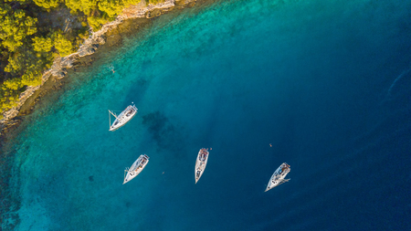 Aerial view of group of sailing boats anchoring next to reef. Bird eye view, water sport theme.