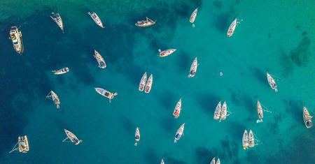 Luchtmening van groep varende boten die op boeien verankeren. Vogelperspectief, watersport thema.