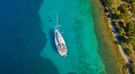 Aerial view of sailing boat anchoring next to reef. Bird eye view, water sport theme.