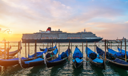 Group of gondolas moored by Saint Mark square with San Giorgio di Maggiore church in Venice, Italy, Europe. Huge transoceanic cruiser on background. Famous historical heritage in Italy.