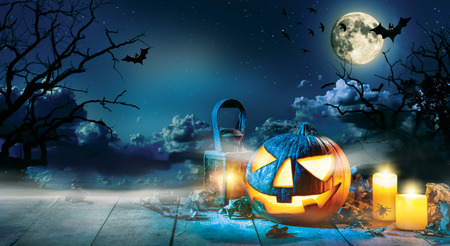 Spooky halloween pumpkin on wooden planks with dark horror background. Celebration theme, copyspace for text. Stock Photo