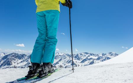 아름 다운 알파인 풍경에 젊은 여자 스키어의 다리의 세부 사항. 겨울 스포츠 및 레크리에이션, 레저 야외 활동.