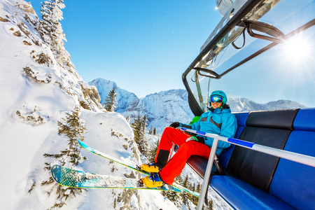 Skier sitting at ski lift in high mountains during sunny day. Winter sport and recreation, leasure outdoor activities.